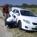 Victor helping one government colleague from Okakarara near Otjiwarongo. His car was lacking a jack. Our vehicle didn\'t had a spanner. Together you can do it!